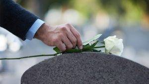 Man putting rose on headstone